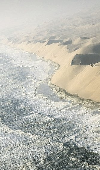 The waves of the Atlantic breaking against the sand cliffs of Namib desert, Namibia
